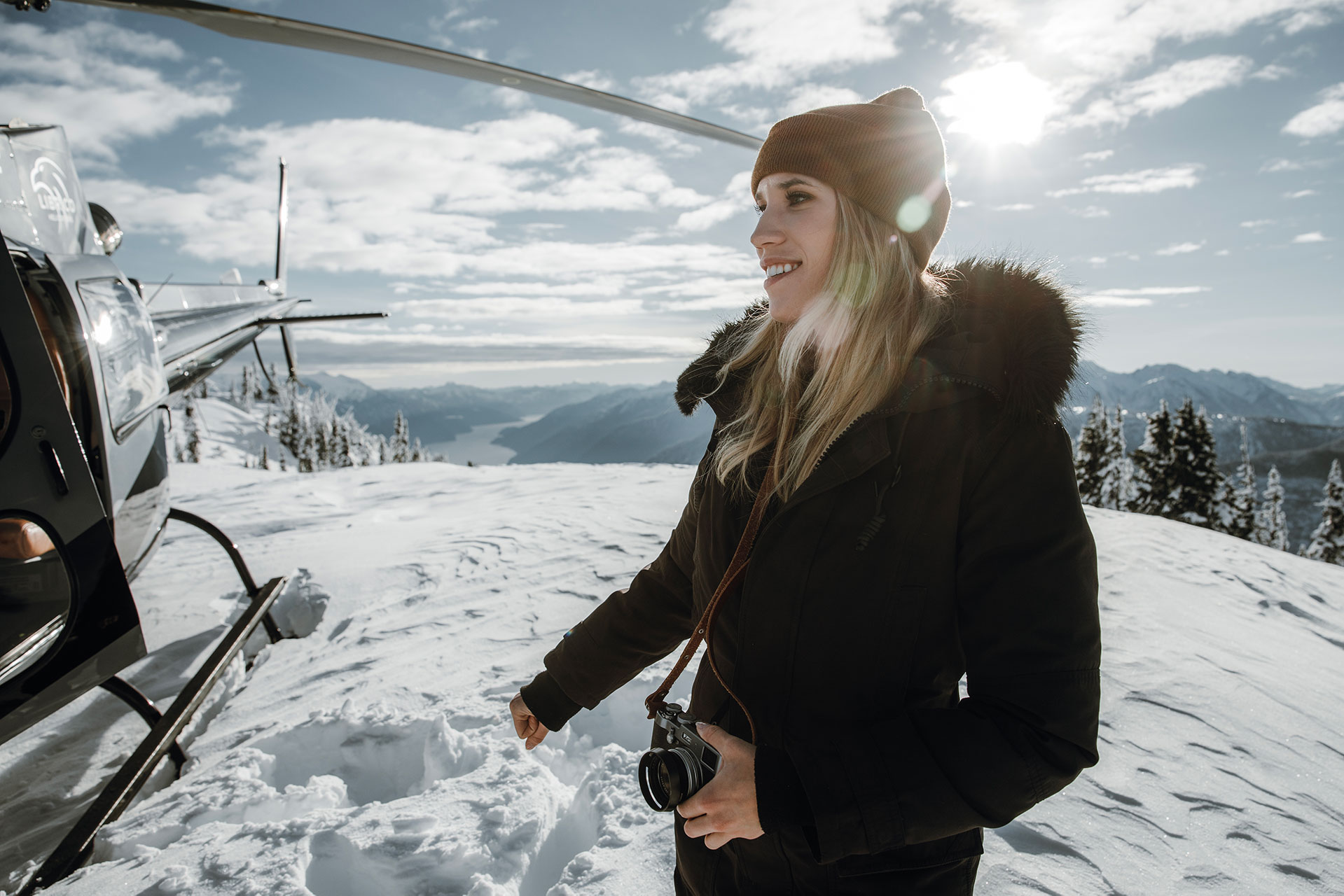 Librico Helicopters team member on a mountain peak with the Falcon Helicopter beside her