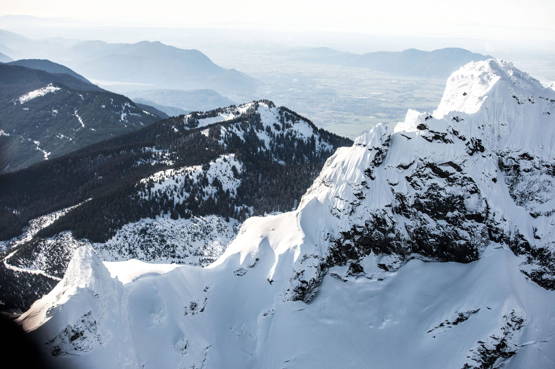 Snowy mountain peak viewed from the Librico Helicopter with the Fraser Valley in the background