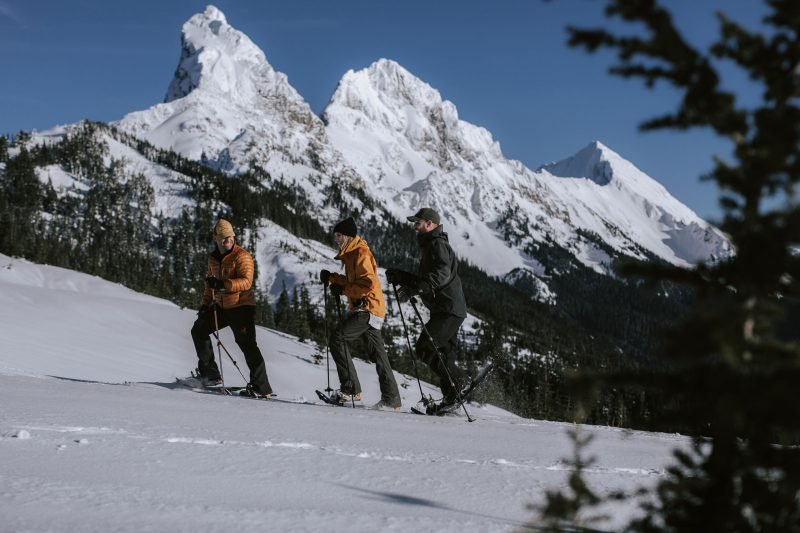 Three Librico Helicopter team members snowshoeing in the mountains.