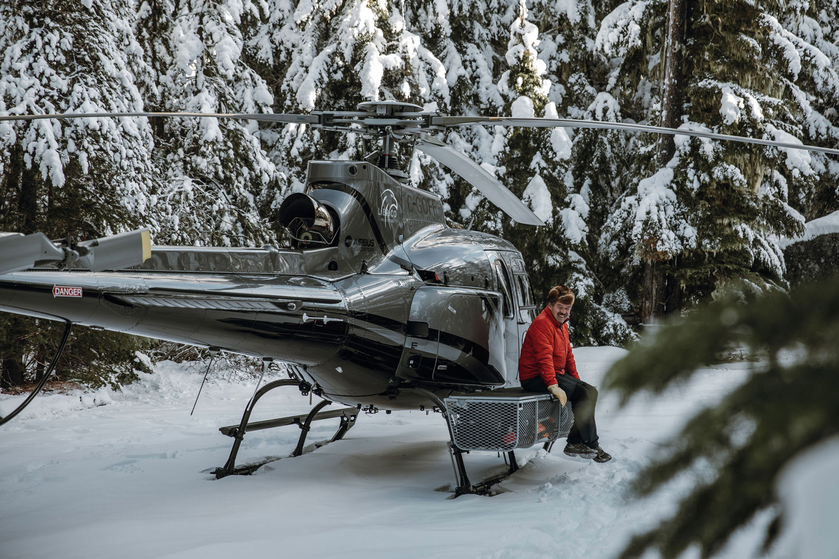 Pilot John Faulkner sitting beside the Falcon helicopter