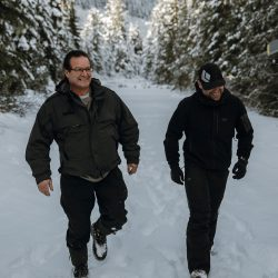 Librico Helicopters team members Don Froese and Adam Palmer walking through the snow.