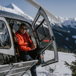 Librico Helicopters pilot John Faulkner sitting in the Falcon Helicopter on a mountain peak
